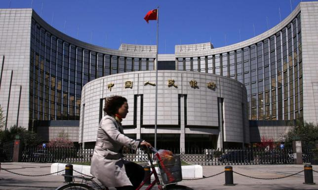 A woman rides past the headquarters of the People's Bank of China (PBOC), the central bank, in Beijing, April 3, 2014. The rare and dramatic slide in the yuan exchange rate that has shaken the outlook for the currency is unlikely to last long as trade rebounds and capital inflows resume. Picture taken April 3, 2014. REUTERS/Petar Kujundzic (CHINA - Tags: BUSINESS)
