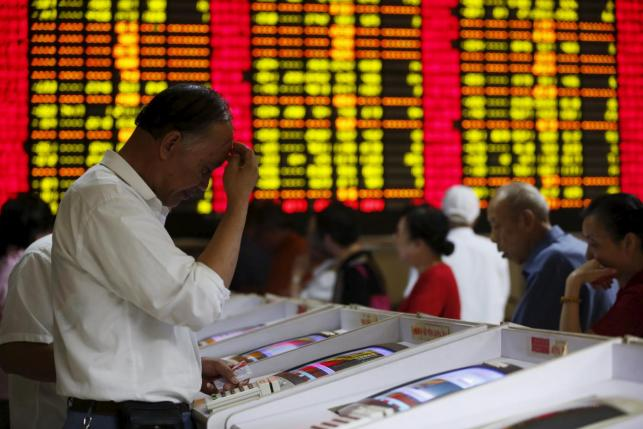 Investors look at computer screens showing stock information at a brokerage house in Shanghai, China, July 8, 2015.  REUTERS/Aly Song